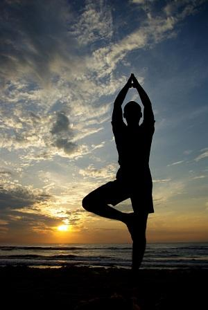Picture of man doing tree pose with sun-set behind him