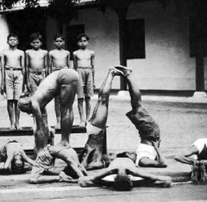 Kristhnamacharya performing yoga on top of a child