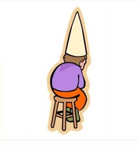 A student wearing dunce cap being disciplined